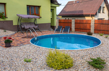 Small Home Swimming Pool With Two Black Sun Loungers And Rocking Bench