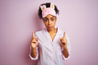 Young african american woman wearing pajama and mask over isolated pink background Pointing up looking sad and upset, indicating direction with fingers, unhappy and depressed.