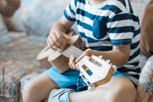 Caucasian child playing and making music chords with small guitar or ukulele, close up - 282940002