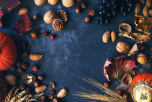 Autumn Or Thanksgiving Background With Decorative Pumpkin, Corn, Nuts, Grapes And Wheat On Dark Stone Table