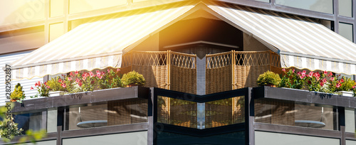 Leinwand Poster  French long balcony with beautiful awning and flowers covered with rays of sun -