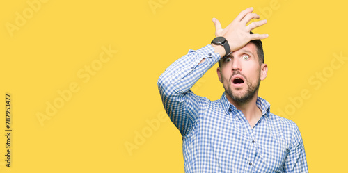 Obraz Handsome business man with blue eyes surprised with hand on head for mistake, remember error. Forgot, bad memory concept. - fototapety do salonu