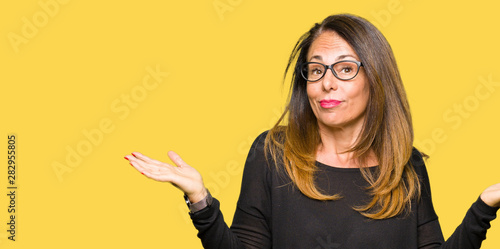 obraz PCV Beautiful middle age woman wearing glasses clueless and confused expression with arms and hands raised. Doubt concept.