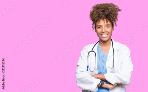 Fotografiet  Young african american doctor woman over isolated background happy face smiling with crossed arms looking at the camera