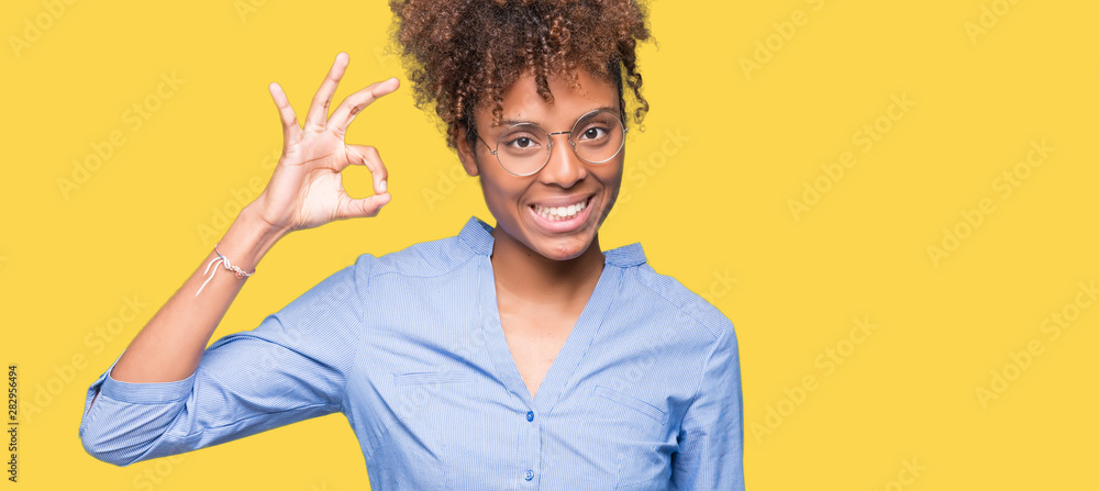 Fototapety, obrazy: Beautiful young african american business woman over isolated background smiling positive doing ok sign with hand and fingers. Successful expression.