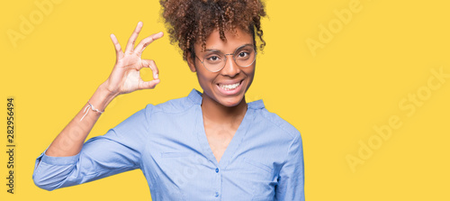 Fotografia  Beautiful young african american business woman over isolated background smiling positive doing ok sign with hand and fingers