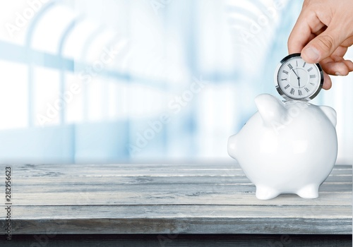 Fotografie, Obraz  Hand depositing  clock  in piggy bank on background
