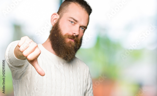 Young hipster man wearing winter sweater looking unhappy and angry showing rejection and negative with thumbs down gesture. Bad expression.