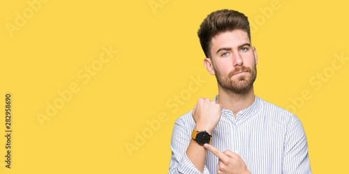 Fototapeta Young handsome man In hurry pointing to watch time, impatience, upset and angry for deadline delay obraz