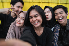 Group Of Young People Selfie Together With Friends In Front Of Yellow Background