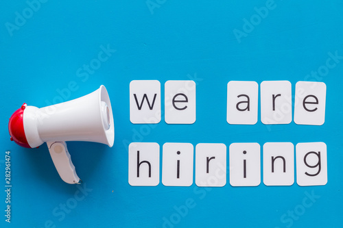 Valokuva  We are hiring announcement with megaphone and text on blue background top view