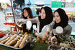 group of young women at a street food restaurant are choosing food