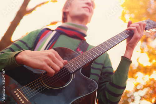 Fotografie, Tablou  Young caucasian man in a sweater playing an acoustic guitar in the autumn forest