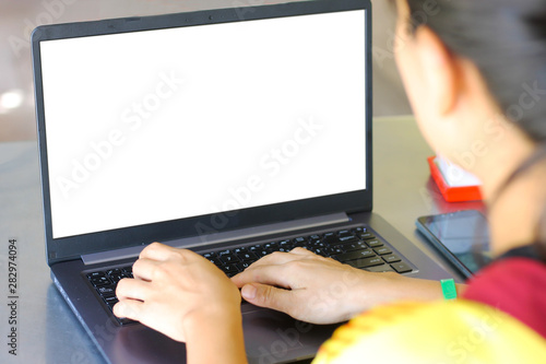 Valokuvatapetti Mock up image of a business woman using and typing on keyboard laptop with blank white desktop screen on work table