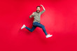 Full length body photo of bearded strong sporty handsome white man wearing grey t-shirt running somewhere with victory while isolated with red background