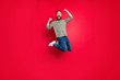 Leinwandbild Motiv Full length body photo of crazy cheerful overjoyed man wearing jeans denim clothes jumping with happiness while isolated with red background