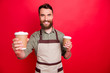 canvas print picture - Close-up portrait of his he nice attractive cheerful cheery friendly bearded guy holding in hands inviting offering espresso latte service isolated over bright vivid shine red background