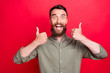 canvas print picture - Photo of excited friendly overjoyed man being glad to have bought something while isolated with red background