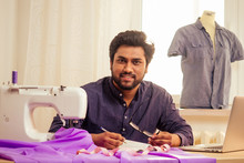 Handsome Indian Tailor Man In A Stylish Shirt Workinh With Violet Cotton Textile At Home Workshop:on The Table A Lamp And A Pot Of Plants