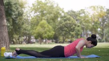 Beautiful Young Woman Doing Yoga Postures On A Fitness Mat In A Garden - Sportswear. Pretty Indian Lady Performing Bhekasana Or Frog Posture With All Her Concentration Under A Tree On A Yoga Mat - ...