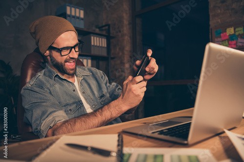 Cool guy work at dark time spending free time playing telephone game wear casual Wallpaper Mural
