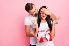 Photo Of Cute Nice Couple Of Fallen In Love Liking To Gift Each Other Red Package With Bow While Isolated With Pink Background