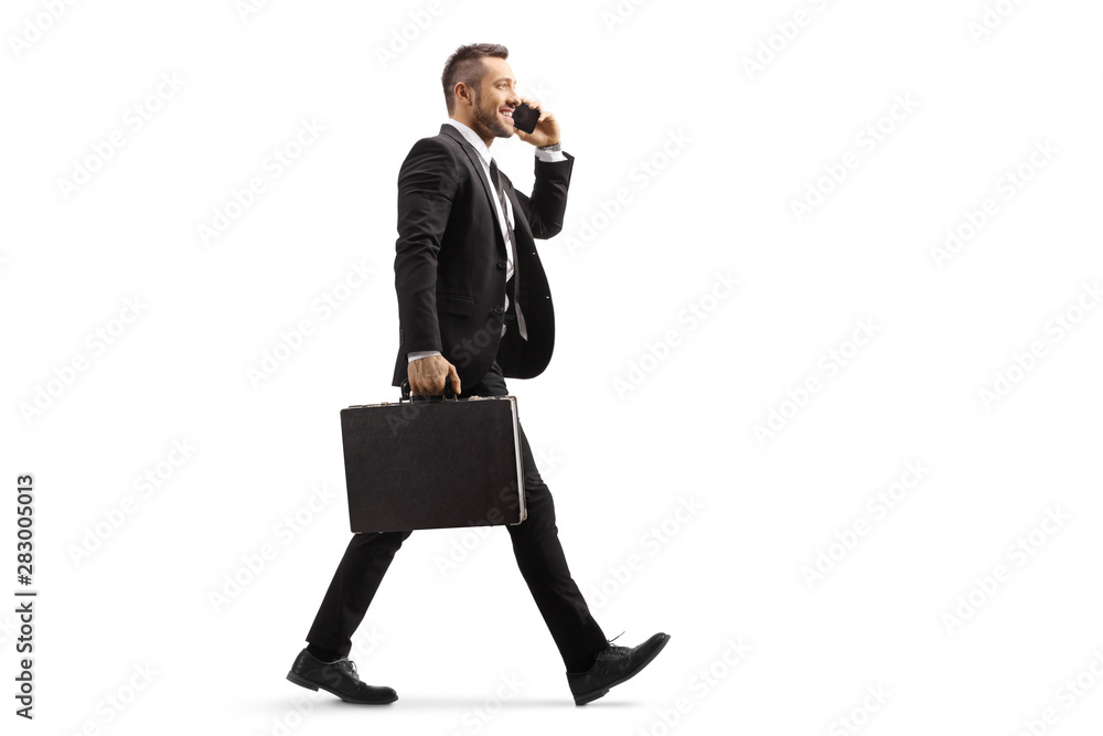Fototapeta Businessman walking and talking on a mobile phone