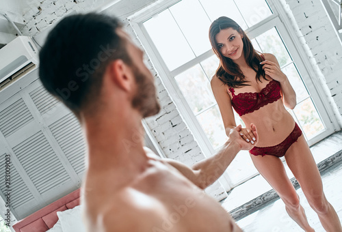The man and woman in underwear standing in the room