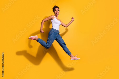 Fototapeta Full length side profile body size photo funny she her dark skin model lady jumping high champion rush sale discount shop wear casual jeans denim pants trousers tank-top isolated yellow background obraz na płótnie