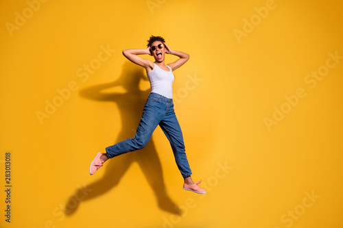 Fototapety, obrazy: Full length side profile body size photo beautiful she her dark skin lady jumping high yell yeah triumphant champion wear casual jeans denim pants trousers tank-top isolated bright yellow background