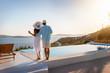 canvas print picture - Romantisches Paar steht am Pool und genießt den Sonnenuntergang bei einem Glas Aperitif während des Sommerurlaubes