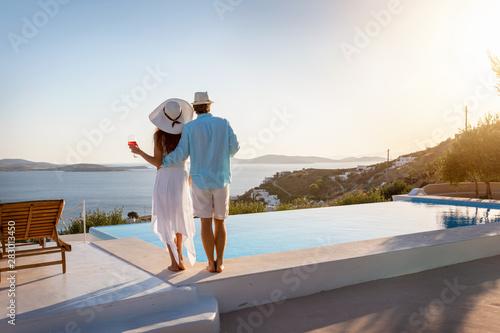 Obraz Romantisches Paar steht am Pool und genießt den Sonnenuntergang bei einem Glas Aperitif während des Sommerurlaubes - fototapety do salonu