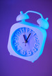 canvas print picture - Light blue alarm clock suspended in air on a bright purple background
