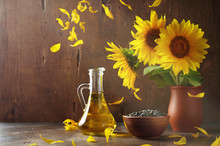 Still Life Of Glass Bottle With Sunflower Oil, Seeds And Flowers In Ceramic Vase