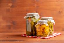 Jars Of Pickled Vegetables: Cucumbers, Tomatoes, Okra, Eggplants On Rustic Wooden Background.