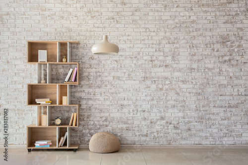 Fotografia  Interior of modern room with bookcase, pouf and lamp
