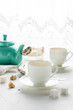 Teal colored tea pot, two white tea cups, sugar bowl on a table by window. Image has copy space