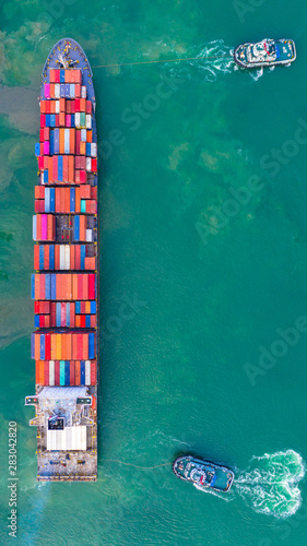 Fotografía  Container ship working at industrial port, Business import and export logistic and transportation of International by container ship in the open sea, Aerial view container ship loading and unloading