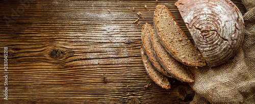 Canvas Prints Bread Bread, traditional spelled sourdough bread cut into slices on a rustic wooden background, close-up, top view, copy space. Concept of traditional leavened bread baking methods