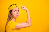 Closeup photo of beautiful lady trying hard to make hand muscle bigger wear casual t-shirt isolated yellow background