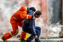 Medium Shot Of Firefighter In Fire Suit On Safety Rescue Duty Help A Man Inside Burning Premises By First Aid Emergency. Safety, Rescue And Health Care Concept.