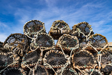 Pile Of Mesh Rope Crab Or Lobster Pots Stacked Up On The Dock, Blue Sky Background