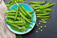 Green, Tender, Fresh And Raw Peas. Close-up And Top View. Rustic Appearance. Rustic Appearance. Black Background.