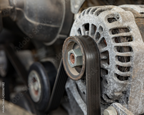 A worn, old serpentine drive belt for motor on alternator pulley on automobile e Canvas Print