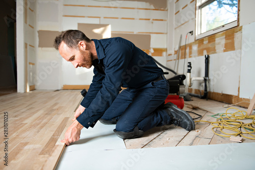 Obraz A Male Worker install wood floor on a house - fototapety do salonu