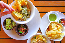 Dipping Yucca Fries With Parsley And Garlic Sauce In Side Dishes Of Guacamole And Salsa