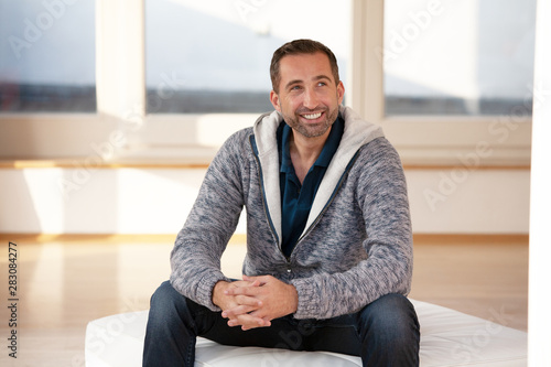 handsome bearded man sitting indoor wearing a cardigan Poster Mural XXL