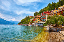 Varenna, Italy. Picturesque Town At Lake Como. Colourful Motley Mediterranean Houses At Stone Beach Coastline Among Green Trees. Popular Health Resort And Touristic Location. Summer Day Landscape.