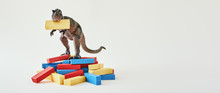 Dinosaur Toy Standing With A Yellow Block In A Mouth On Multi-colored Wooden Blocks