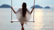 Smiling Woman In A White See-through Dress Sitting On A Wooden Swing. Full Shot.
